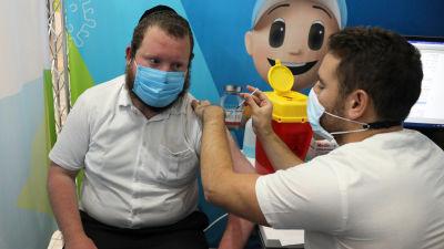 En sjukskötare som ger en man en tredje vaccindos.