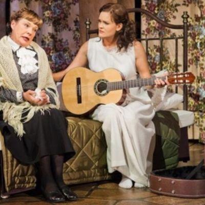 Kaksi naista istuu sängyllä. Nuoremmalla naisella on kitara.