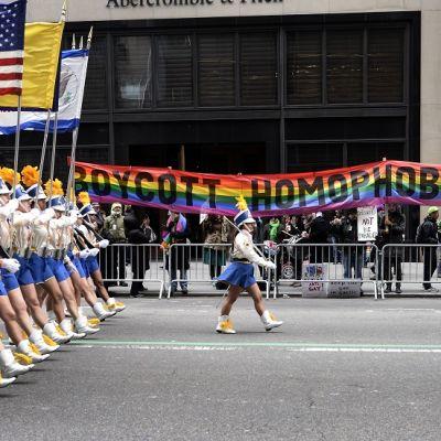 Paraatiasuiset tytöt kantavat lippuja kadulla, jnka varrella on sateenkaarijulistetta kannattelevia ihmisiä.