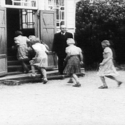 Lapset juoksevat koulurakennukseen sisälle jonossa.
