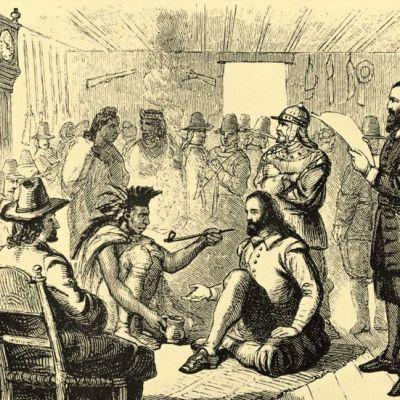 Puukaiverruskuva lattialla istuvista miehistä, joiden ympärillä seisoo ja istuu intiaaneja ja englantilaisia.