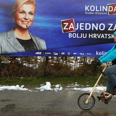 mies ajaa pyörällä vaalijulisteiden ohi