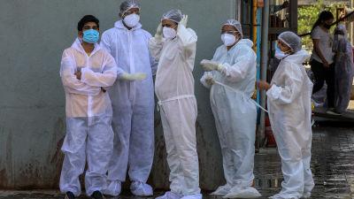 Työntekijät viettävät taukoa sairaalan ulkopuolella Intiassa.
