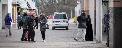 människor och en polisbil står vid köpcentret i Gårdsbacka.