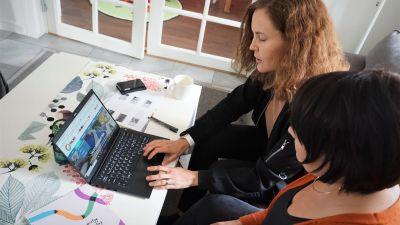 Två kvinnor sitter i en soffa och tittar på en dator.