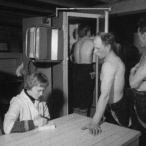 Miehet jonottavat terveystarkastuksessa vuonna 1964.