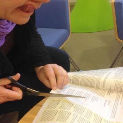 Nainen leikkaa lehteä kieli ulkona suusta.