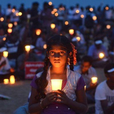 Joukko ihmisiä pitelee kynttilälyhtyjä illan hämärässä.  Kuva on tarkennettu nuoreen vakavailmeiseen tyttöön.