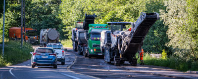 Män och maskiner jobbar med att asfaltera