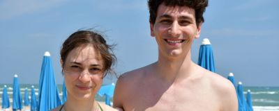 En ung kvinna och hennes kille står och håller om varandra på stranden och tittar in i kameran. Hon har en grön bikini på sig, han är barbröstad. I bakgrunden syns solstolar.
