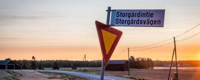 En skylt med texten Storgårdsvägen, i bakgrunden syns åkrar och en väg i soluppgången