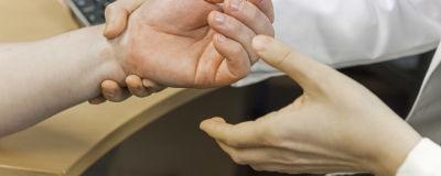 Ett par läkarhänder och en patients hand. I bakgrunden ett tangentbord.