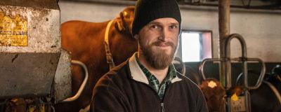 En jordbrukare i förgrunden, kor skymtar i bakgrunden