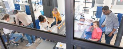 Personer jobbar på ett kontor. Bilden är fotograferad ovanifrån.