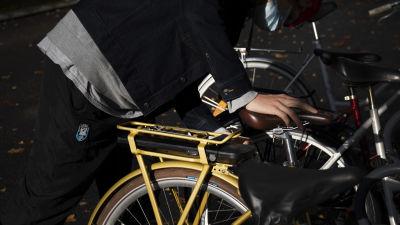 Sähköpyörän akkua laitetaan paikoilleen tarakan alle.
