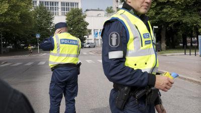Två polisen står på vägen, redo att utföra blåstest på bilförare. Deras ansikter syns inte.