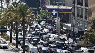 Massor av bilar som köar kors och tvärs. De köar till en bensinstation.