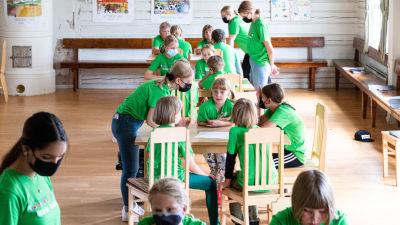Barn som sitter vid bord i en sal.