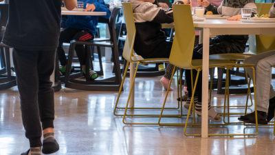 Inne i Vårberga skolas matsal. På bilden syns barn som sitter vid bord med matbrickor framför sig.