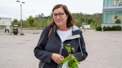 Anne Elenius-Parkkari har en vit plastpåse med björkplantor i.