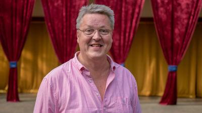 En man i rosa skjorta. I bakgrunden en teaterscen. Han är glad.