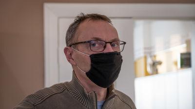 En man med svart munskydd tittar in i kameran
