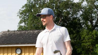 Jonathan Andersson utomhus vid golfplan med golfklubba i handen.