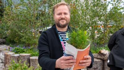 Thomas Weissman håller fram tallplantor som lindats in i tidningspapper.