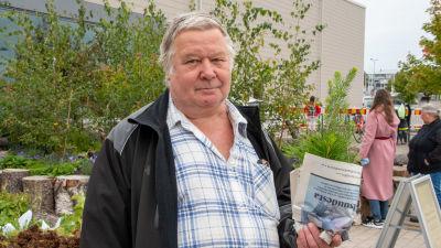 Hannu Lehto håller i gran- och tallplantor inlindade i tidningspapper.