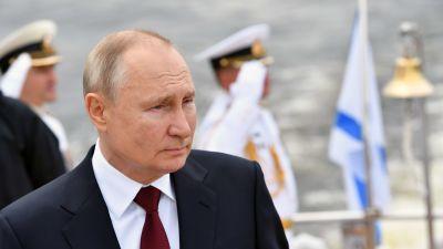 Bild på Rysslands president som står framför marinsoldater.