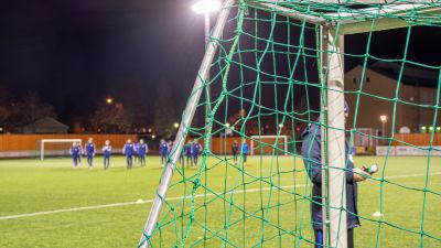 Kanten av ett fotbollsmål. I bakgrunden syns fotbollsplanen och FC Futuras herrlag.