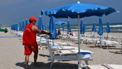 Lorenzo Paupini säsongsarbetar som badvakt på stranden på förmiddagarna och driver en bar på kvällarna. Nu går han på stranden och fäller upp parasollen och ser till solstolarna.