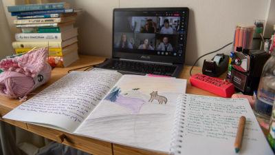 Studentlya med skrivbord där det ligger böcker, dator och anteckningar. På datorskärmen pågår digital föreläsning.