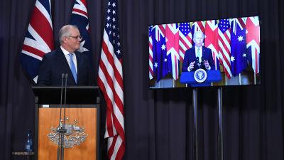 Australiens premiärminister Scott Morrison står och lyssnar på USA:s president Joe Biden som han talar med via videolänk.