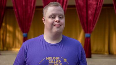 En ung man med blålila t-skjorta. Bakom en teaterscen utomhus. Han ser glad ut.