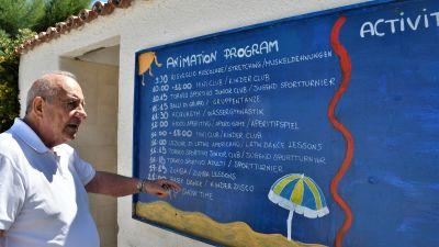 Amedeo Tarsi står framför en tavla med barnprogram skriven med kritor.