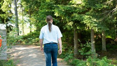 Kristian Meurman går på en sandväg i en skogig miljö.
