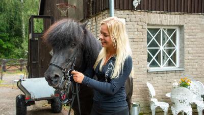 Arnella Nyman med sin mörkbruna islandshäst framför sitt stall.
