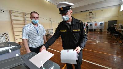 En kadett i uniform röstar i en gymnasiksal i Vladivostok.