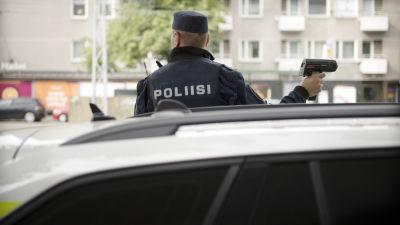 Poliisi mittaa ajonopeutta kadun varrella.