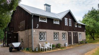 Ett brunt stall med vita fönsterkarmar och grått tegel nertill.