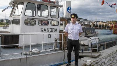 Albert Lass står i kaptenshatt och vit skjorta framför skeppet Sandra D.