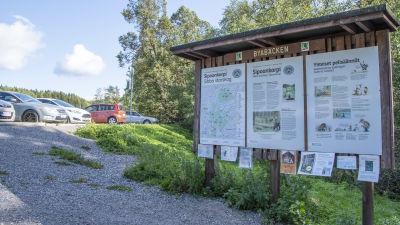 En skylt som det står Byabäcken på och innehåller infromation som Sibbo storskog. I bakgrunden ser man bilar på en parkeringsplats.