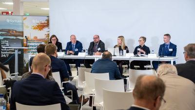 Fortums informationstillfälle på Lovisavikens skola. På bilden syns publik som sitter på stolar på rad och längst fram sitter en panel med personer vid ett långt bord.