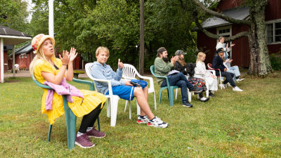 Barn som sitter på rad och applåderar.