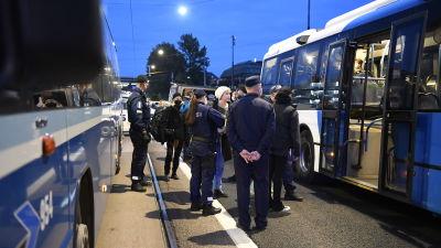 Poliisit ohjavat bussiin ympäristömielenosoituksessa kiinniotettuja.