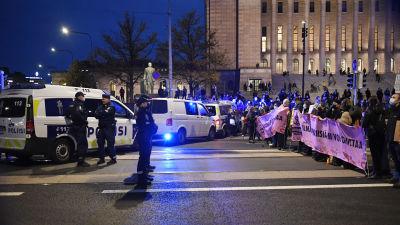 Poliisit ja Elokapinan mielenosoittajat ovat vastakkain Eduskuntatalon edessä iltapimeällä.
