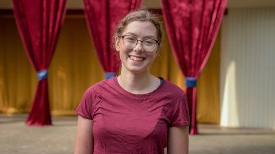 En ung glasögonprydd kvinna i hallonröd t-skjorta. Bakom en teaterscen. Hon ser glad ut