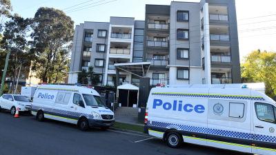 Polisbilar utanför bostadskomplex.