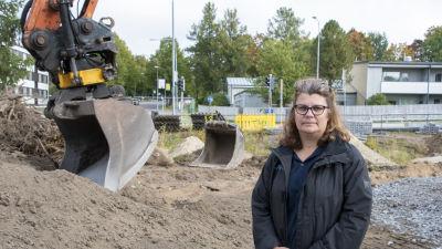 Catarina Helenius står framför en grävskopa som är beredd att börja bygga de nya bostäderna i hörnet av Alexandersgatan och Sibeliusbulevarden i Borgå.
